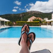 Stock image of a woman's feet by a pool in Greece on 14 July 2019 thumbnail