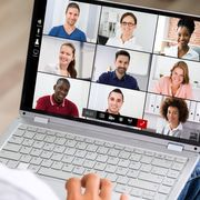 File image of a worker looking at faces of several colleagues on screen thumbnail