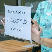 File image of woman placing a 'Closed' sign on a cafe thumbnail