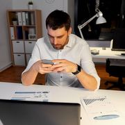 File image of a man looking at his phone in front of his laptop thumbnail