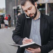 Man on phone writing notes while walking thumbnail