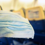Plane passenger holding a mask thumbnail