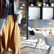 Woman carrying coffee and laptop heading to work thumbnail