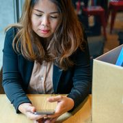 A woman who has resigned sits looking at her phone thumbnail