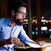 Man eating noodles at his desk thumbnail