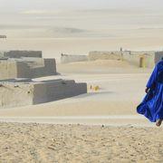 Man in blue robes walking in the Saharan Desert town of Araouane thumbnail