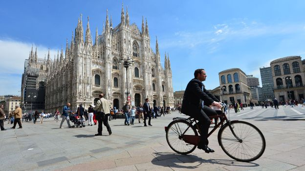 A cyclist rides through Milan's piazza del Duomo (Credit: Giuseppe Cacace/AFP/Getty)