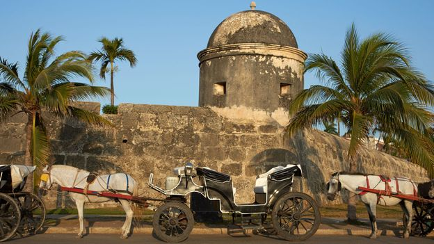 Horse-drawn carriages wait in front of Cartagena's fortress walls (Credit: Credit: Jeremy Richards/Thinkstock)