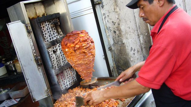 The pork is marinated, roasted by an open flame and carved off (Credit: Credit: Kent Wang/Torta Brava/Flickr/CC BY-SA 2.0)