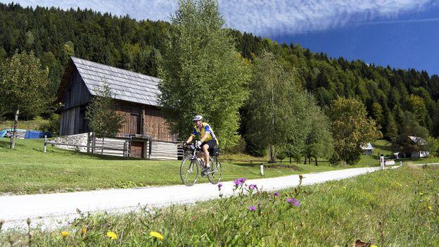 A single cyclist rides Bohinj's quiet country roads (Credit: Credit: Rebecca E Marvil/Getty)