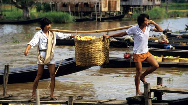 Market workers disembark from a boat carrying baskets full of tomatoes on Inle Lake (Credit: Credit: incamerastock/Alamy)