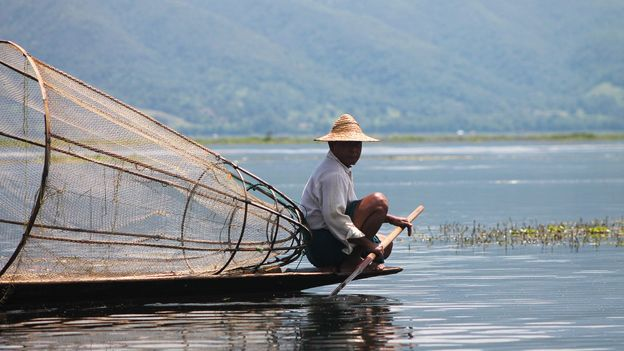 A rower rests his legs on the tranquil Inle Lake (Credit: Credit: Adrienne Jordan)