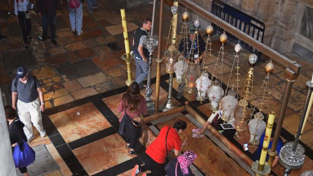 Tourists and pilgrims kiss the Stone of Unction, on which they believe Jesus was washed before burial (Credit: Credit: Sara Toth Stub)
