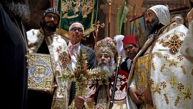 A Coptic church leader guides a Palm Sunday procession (Credit: Credit: Gali Tibbon/AFP/Getty Images)