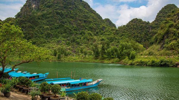 Long boats lead travellers from the quiet village of Phong Nha along the river to the Phong Nha cave (Credit: Credit: Kim I Mott)