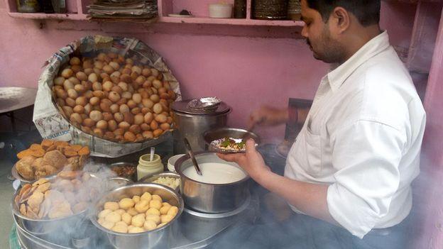 Pani puri sellers dip the puris into various bowls of fillings and chutneys (Credit: Credit: Charukesi Ramadurai)