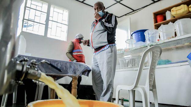 Gatikabisi boils some of the raw milk on site at Kuruhimbi (Credit: Credit: Dan Nsengiyumva)