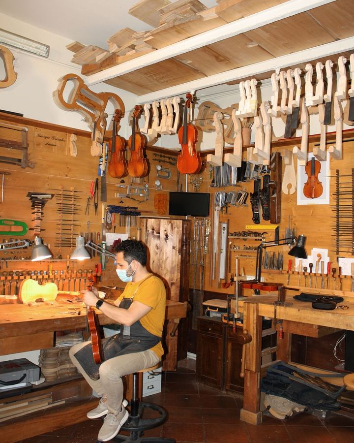 One of three young craftsmen at work in the bottega of Giorgio Grisales, the president of the city's 'Antonio Stradivari' Consortium of violin makers (Credit: Michela Vado)
