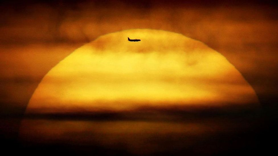 An airplane passes in front of the setting sun in London. A flight does not always divert if someone expires onboard. (Press Association)