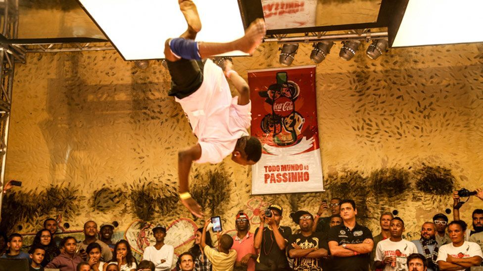 A dancer at the Passinho battle in the Vidigal favela soars above the watching crowd. (Maria Buzanovsky)