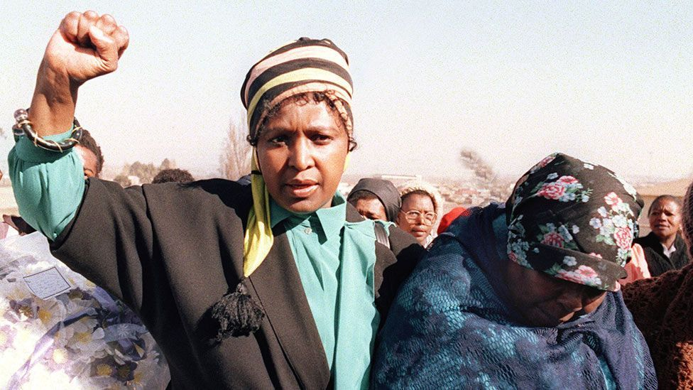 Winnie's more militant look, worn as she raises a clenched fist during the 1987 funeral of Sello Motau, senior member of the ANC military wing. (Getty Images)
