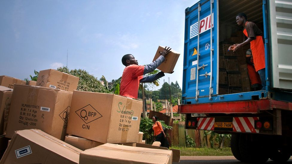 At Barefoot Power's office in Kampala, Uganda, employees help unload a container of products from China, via Nairobi, including lights and power packs.