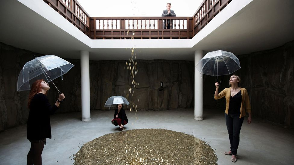 In the Russian pavilion, a shower of coins rains on female visitors in an installation by Vadim Zakharov. (Daniel Zakharov)