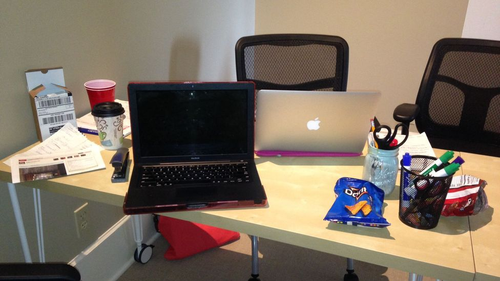 Empty snack bags and coffee cups on a shared worktable. (Influence & Co.)