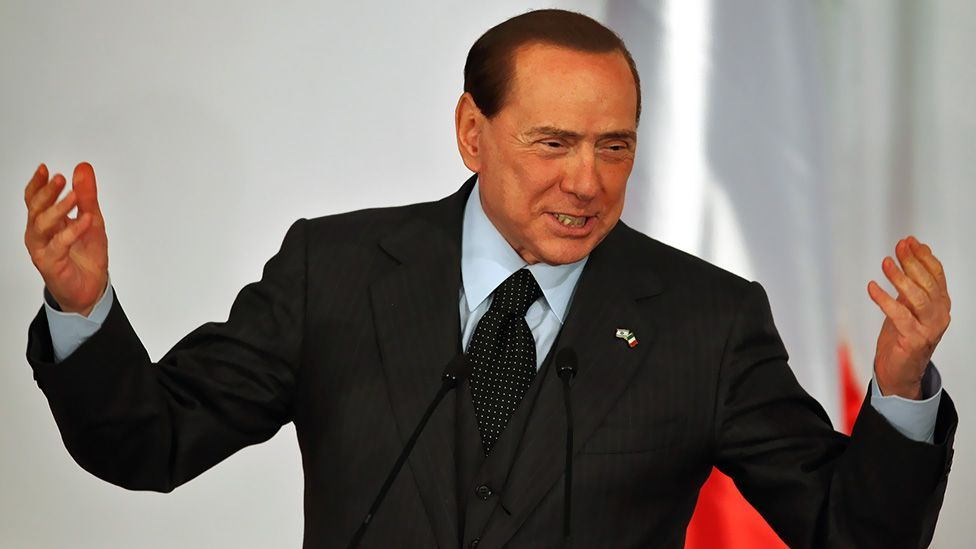 Berlusconi wears a customary two-piece suit as he gestures during a press conference in Jerusalem, Israel in 2010. (Getty Images)