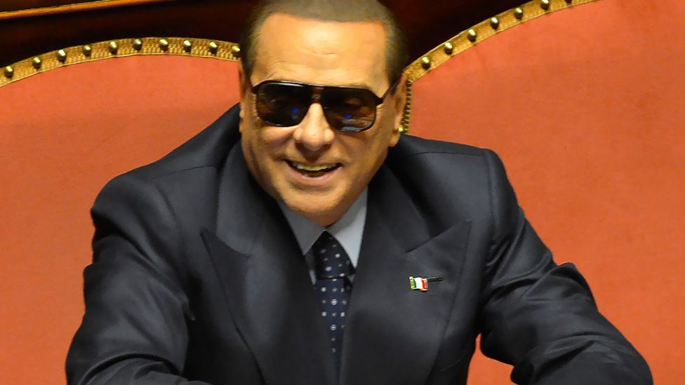 Berlusconi smiles as he wears sunglasses to hide an eye infection during a hearing for his trial at the Senate in Rome this year. (AFP/Getty Images)