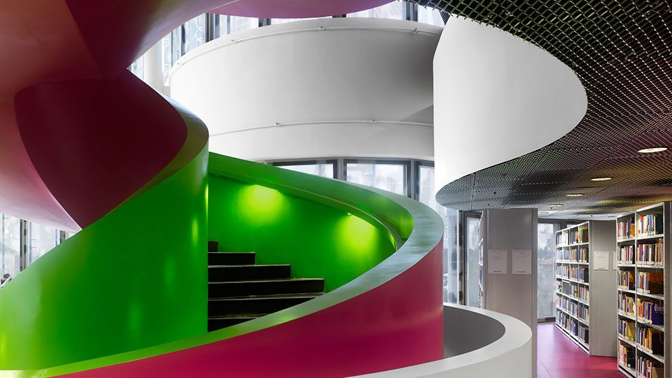 A brightly coloured concrete staircase winds its way through the library of the Brandenburg Technical University in Cottbus, Germany.