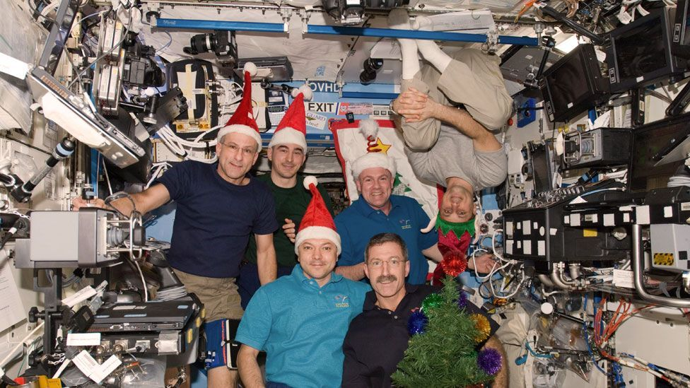 The Expedition 30 crew members indulge in a little Christmas fun for the camera. (Nasa)