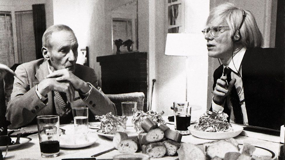 William S Burroughs and Andy Warhol having dinner at New York's Chelsea Hotel.