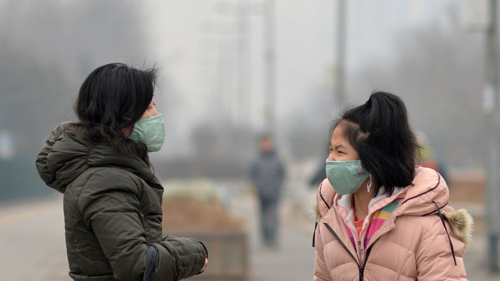 Residents wearing masks in smog-covered Beijing. (STR/AFP/Getty Images)