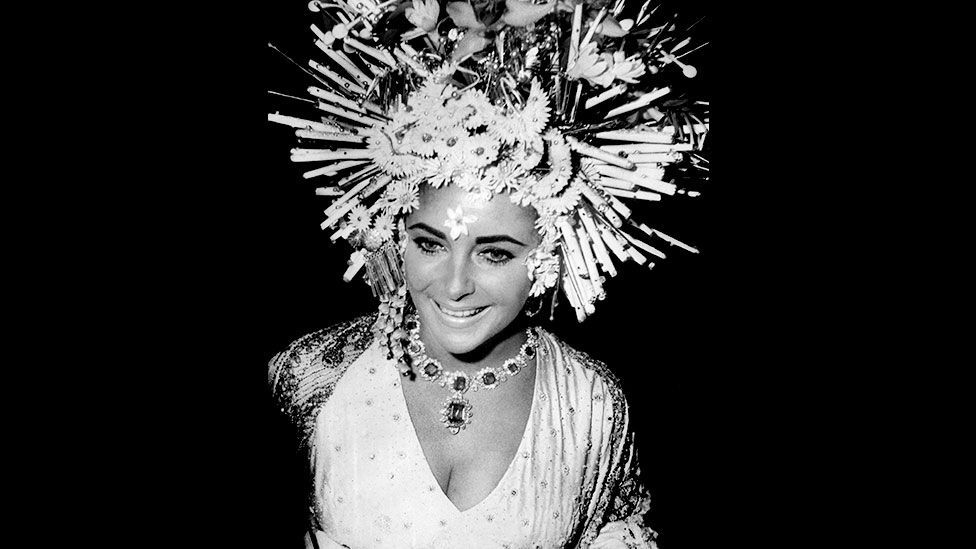Elizabeth Taylor wears Bulgari jewellery at the masked ball, Hotel Ca'Rezzonico, Venice, 1967. Bulgari was founded in Rome in 1884, and has since become a global brand. (V&A)
