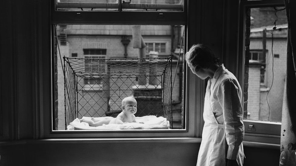 In the 1930s, baby cages were installed on the outside of apartment blocks, to give them fresh air and sunlight. (Getty Images)