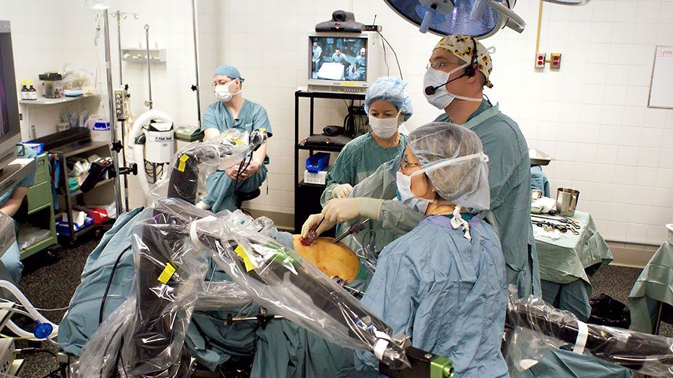 Surgery underway in Ontario... controlled by Mehran Anvari on the screen behind, 400km away (St Joseph's Healthcare)
