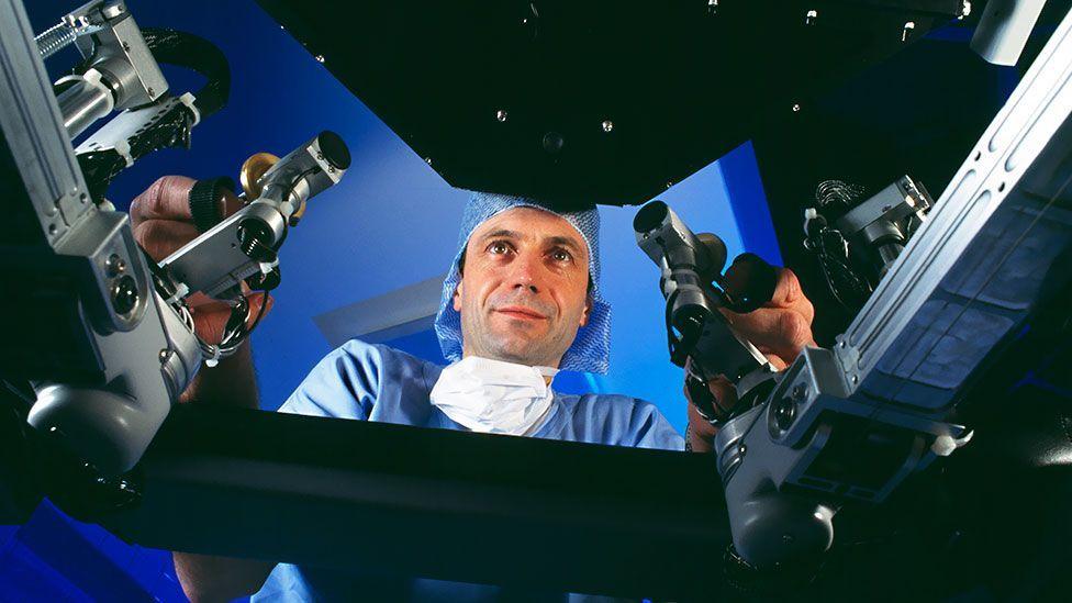 A surgeon controls the Da Vinci robot surgeon, viewing a 3D image of the body (SPL)