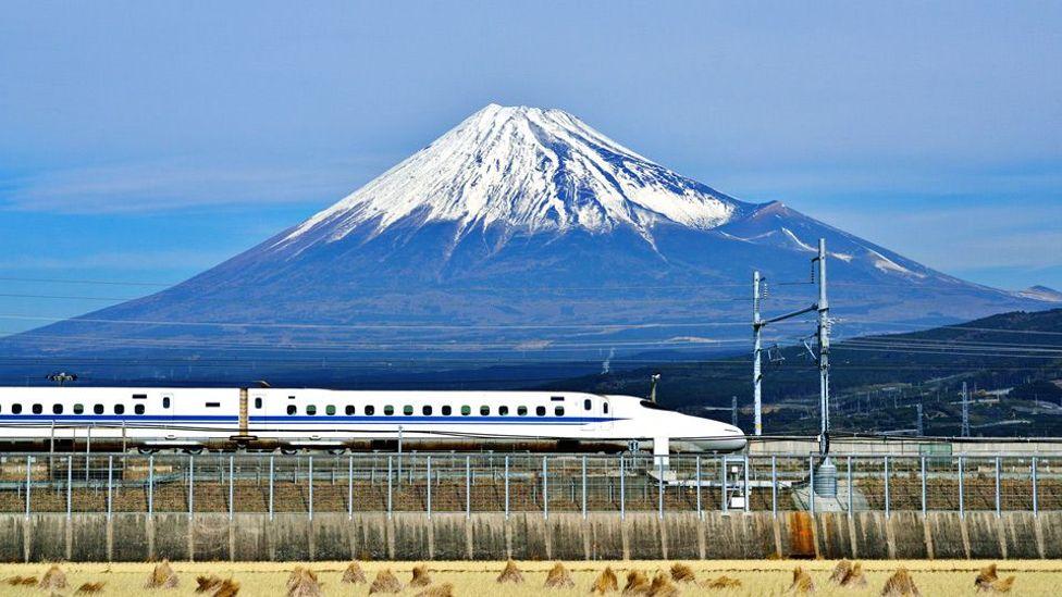 A bullet train speeds past a majestic Mount Fuji in Japan (Sean Pavone/Alamy)