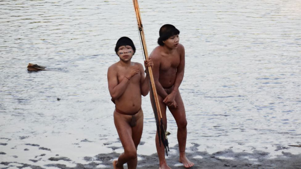 Two members of an isolated indigenous tribe from the Amazon investigate a settled community of villagers in Acre, Brazil (Funai)