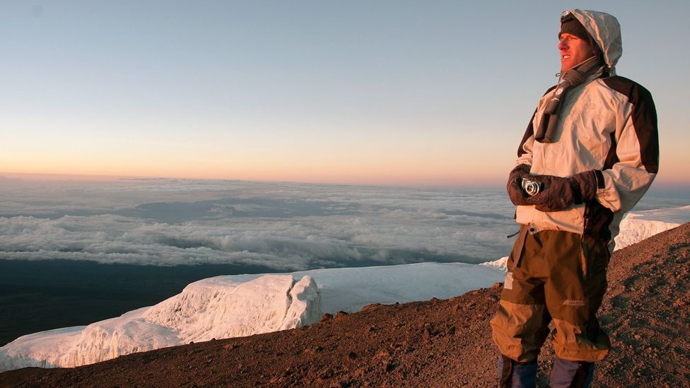With a tool of the trade in hand, Dan enjoys the sunrise from the peak of Mt Kilimanjaro. (Audrey Scott)
