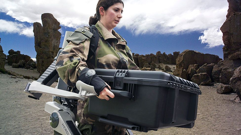 The Hercules robotic exoskeleton helps a female soldier lift a heavy load (SPL).