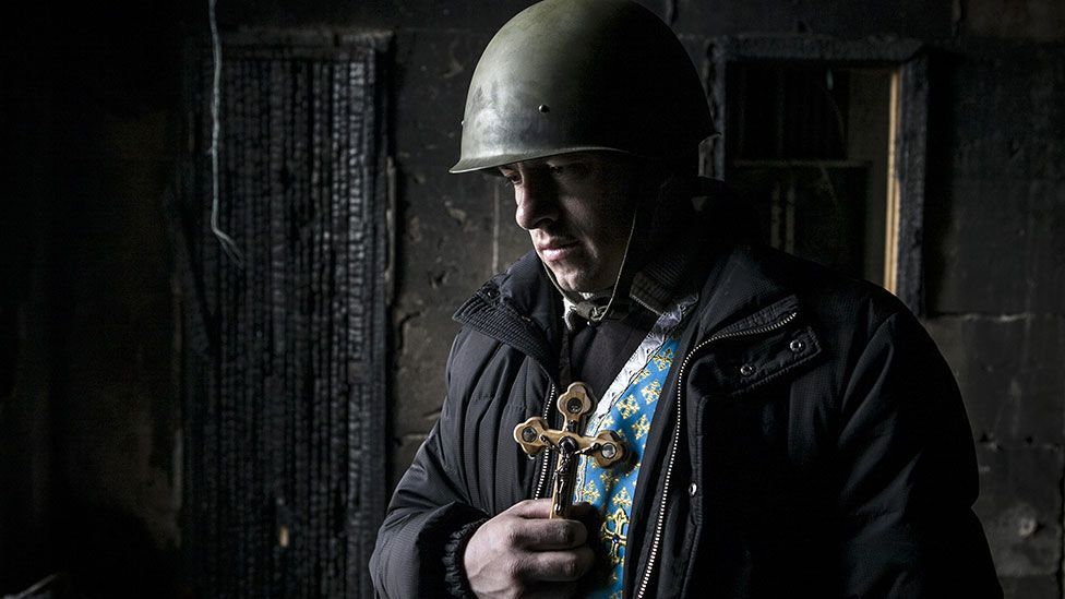 A priest in Ukraine holds a cross in the ruins of Kiev's Trade Union building earlier this year (Getty Images)
