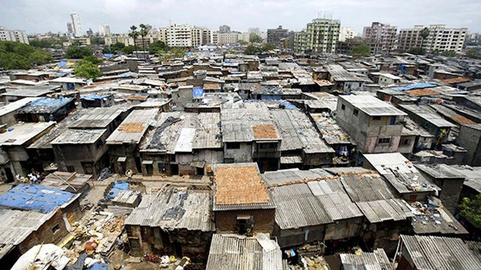 The sights and sounds of the slums in Mumbai, India showed Simon Huggins how different life could be to his hometown of Banbury, England. (Getty)