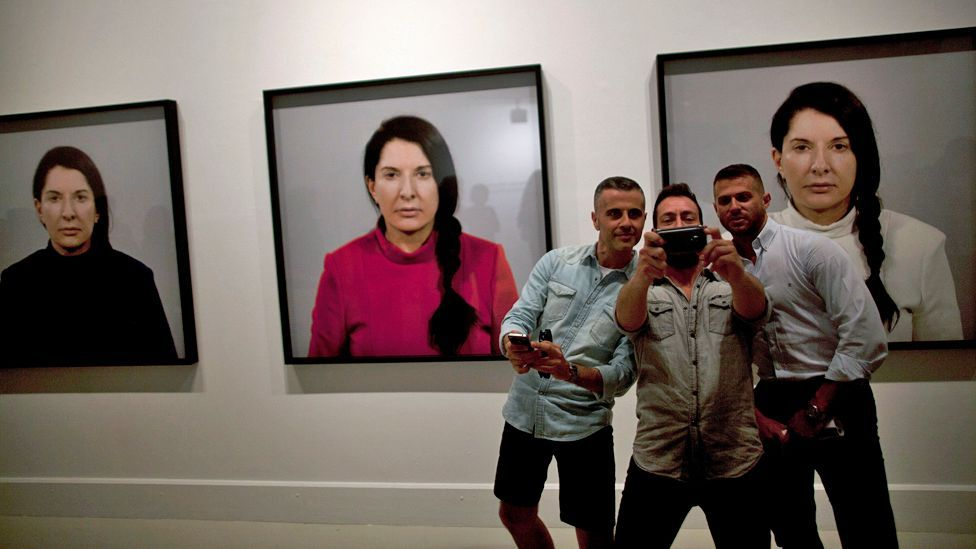 A group of visitors to the Contemporary Art Center in Malaga, Spain, take a selfie in front of photos of Marina Abramović (Corbis)