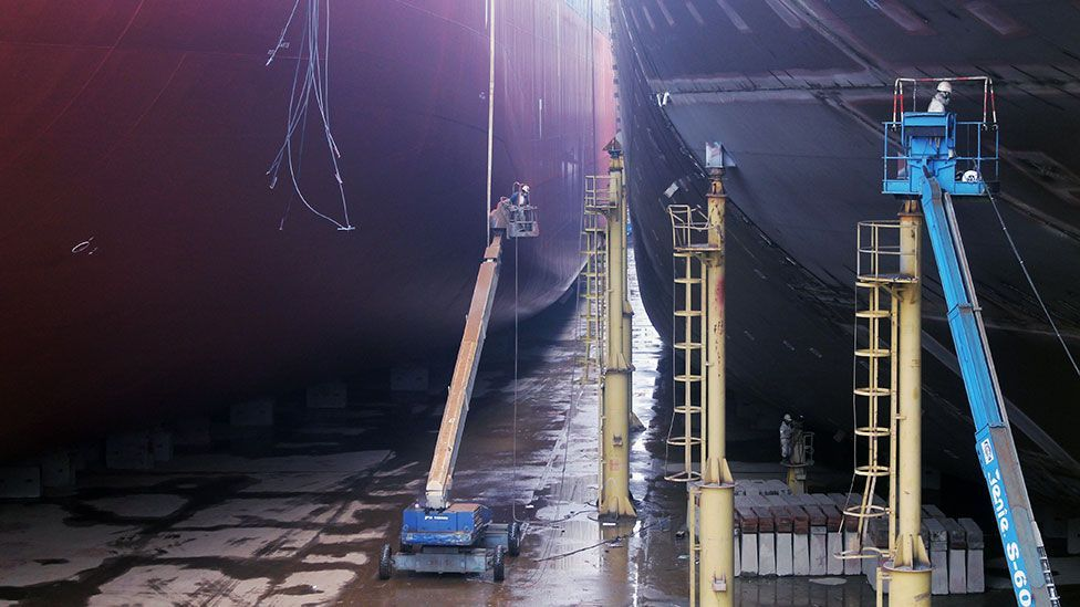 Welders connect massive steel sections of a container ship in the Shanghai Shipyard dry dock (Liam Young/Unknown Fields)