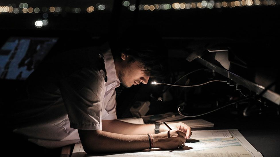 A crew member updates navigation charts (Kate Davies/Unknown Fields)