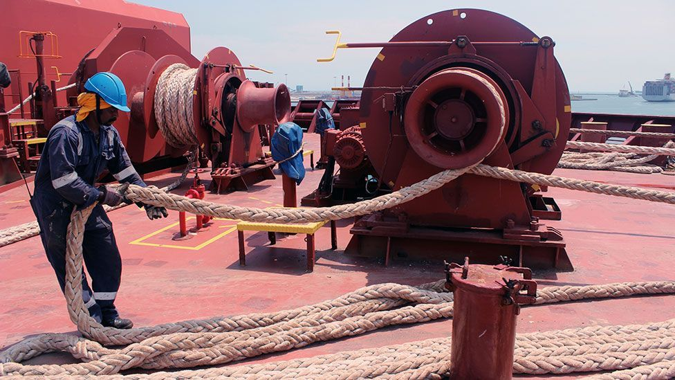 An Indian crew member of the Maersk Seletar lets out the bow rope before anchoring in Kaohsiung Port, Taiwan (Liam Young/Unknown Fields)