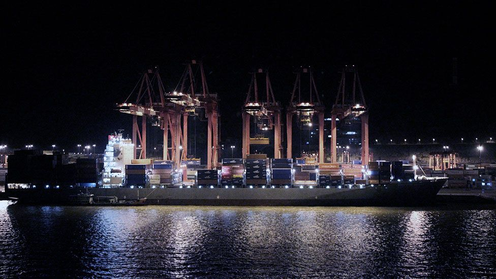 A container ship is loaded by night in a Shanghai port (Liam Young/Unknown Fields)