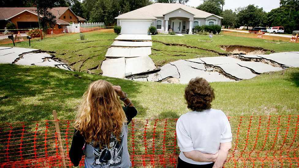 A mother and daughter look at the damage in Spring Hill, Florida (Alamy)